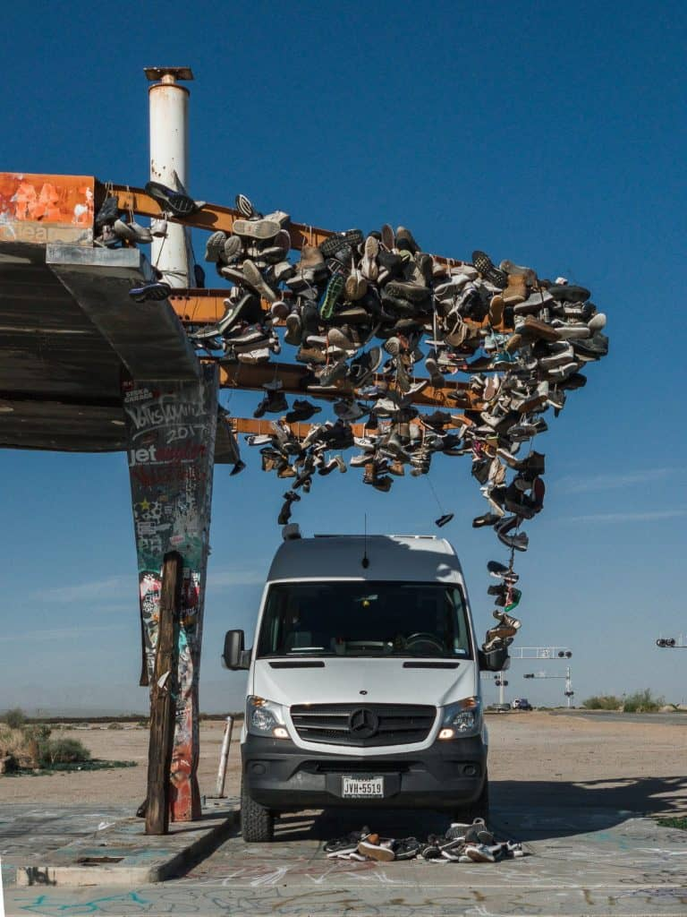 The white Sprinter van parks under an awning covered with undreds and hundreds of shoes.