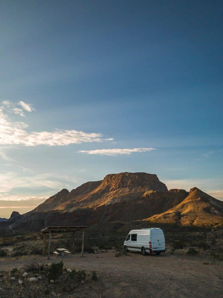 The white Sprinter camps out in Big Bend State Park. There is a large butte off in the distance.
