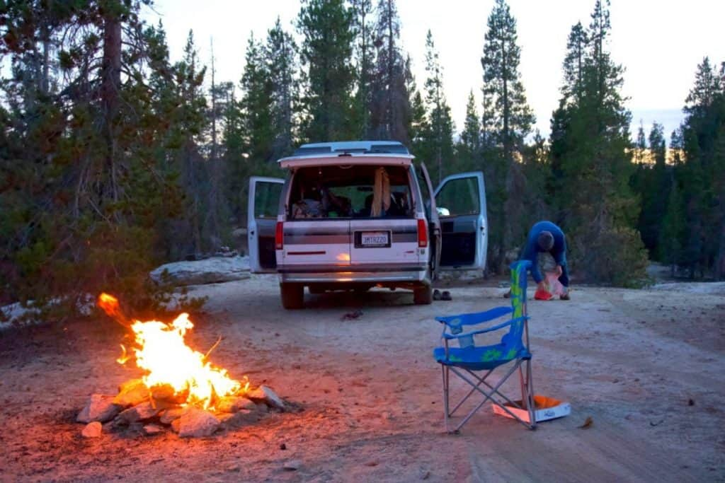 The van is camped out for the night, there is a fire bruning large with a chair in front of it. They appear to be camped in the middle of the woods.