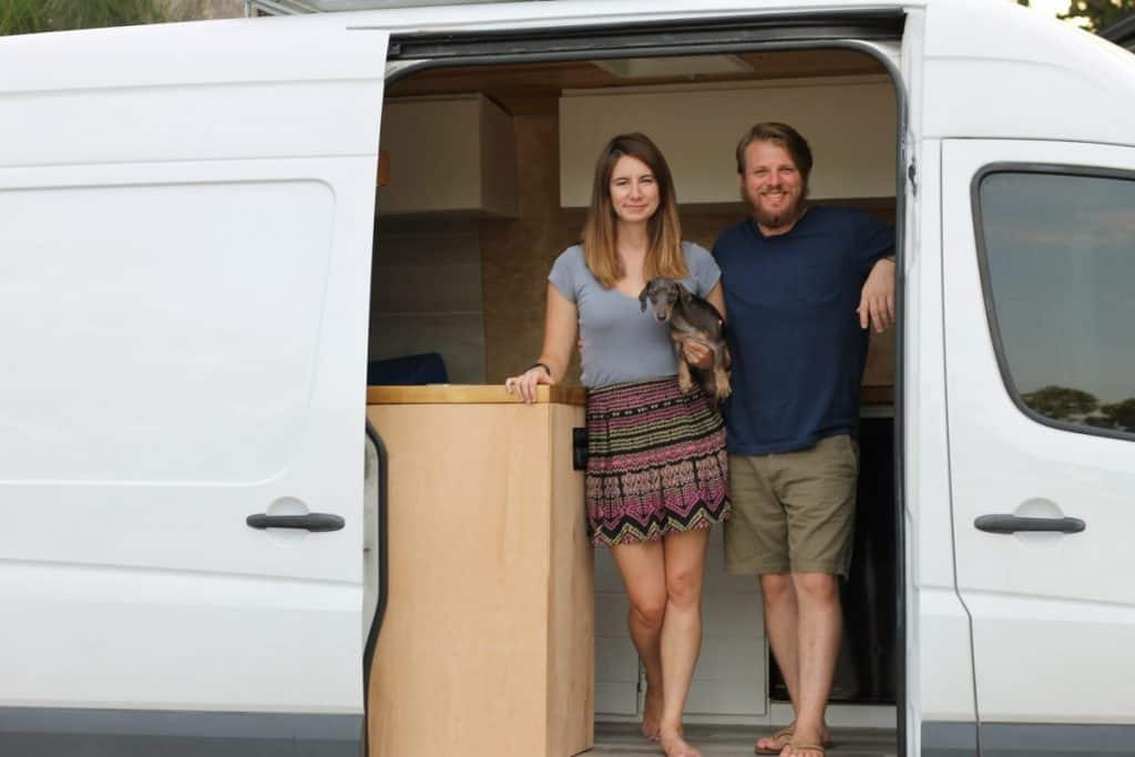 Girl and guy stand inside their Sprinter van built to be a tiny home. The side door is open and they stand in the opening next to their kitchen counter.
