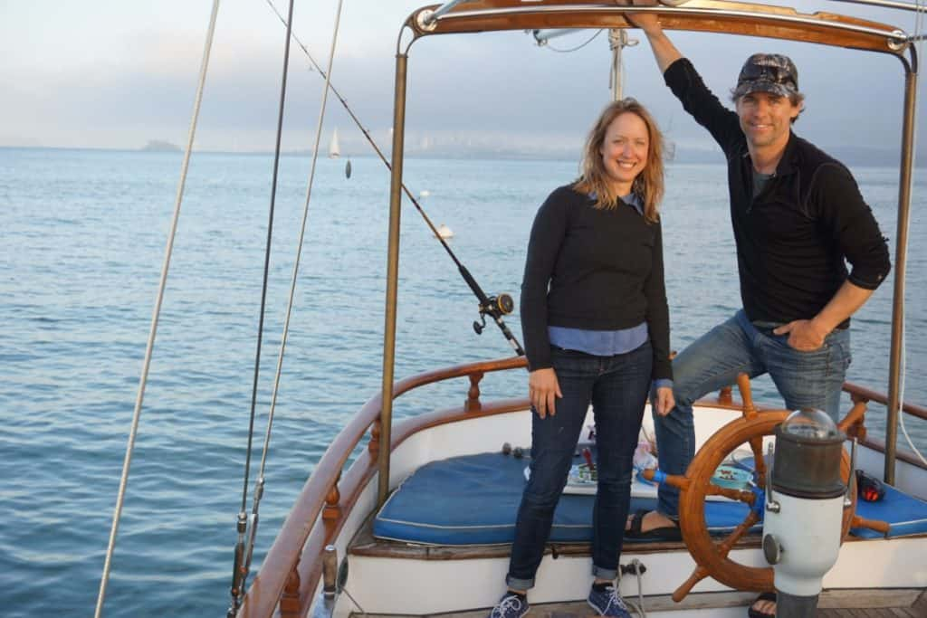 Girl and guy stand on their sailboat. There is a fishing pole behind them.