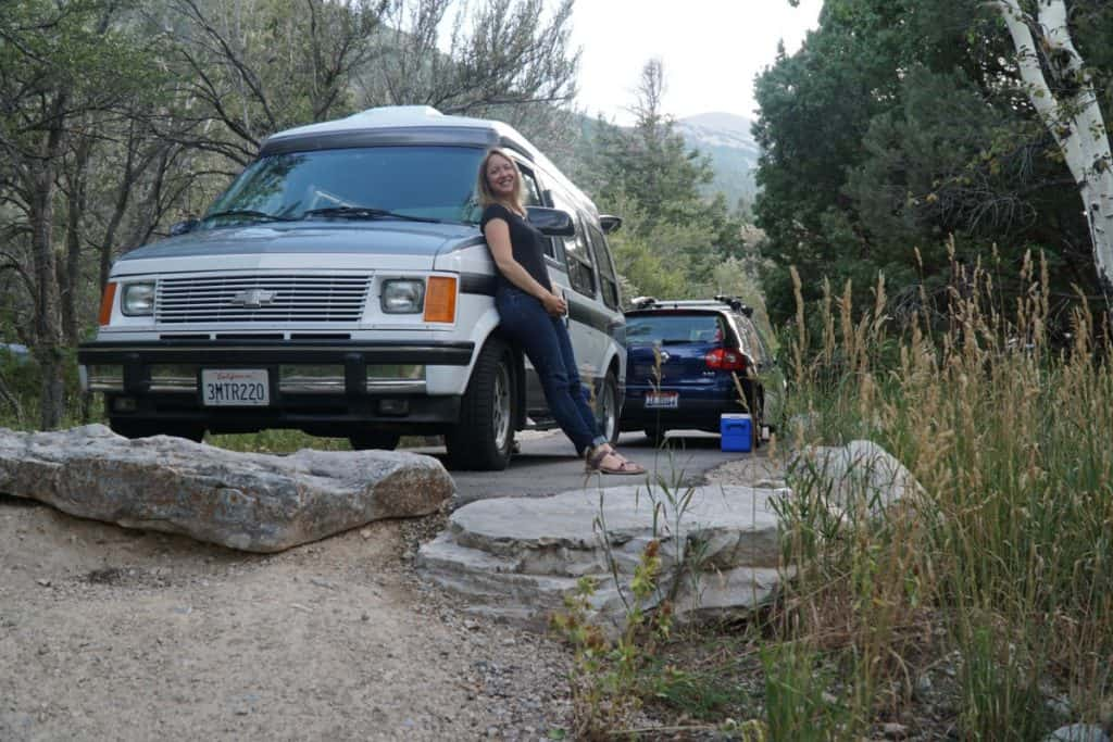 Girl casually leans against her van in the woods.