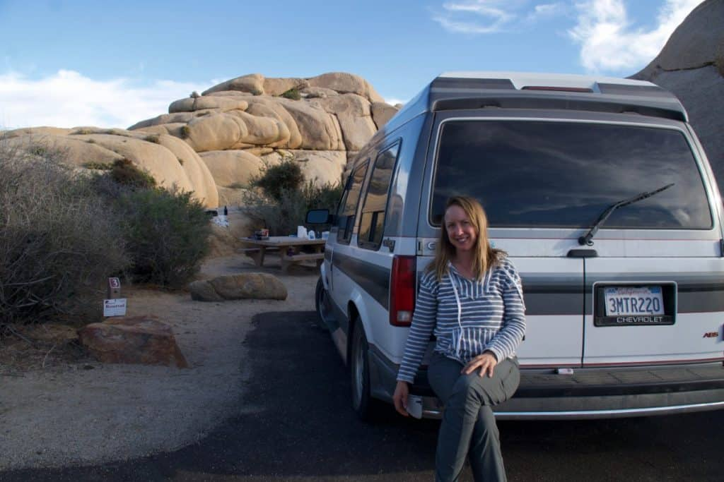 Girl sits on the bumper of her van with a large rock formation behind them.