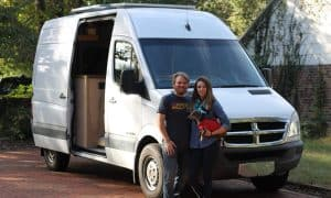 Girl and guy stand in front of white sprinter van holding a small dog.