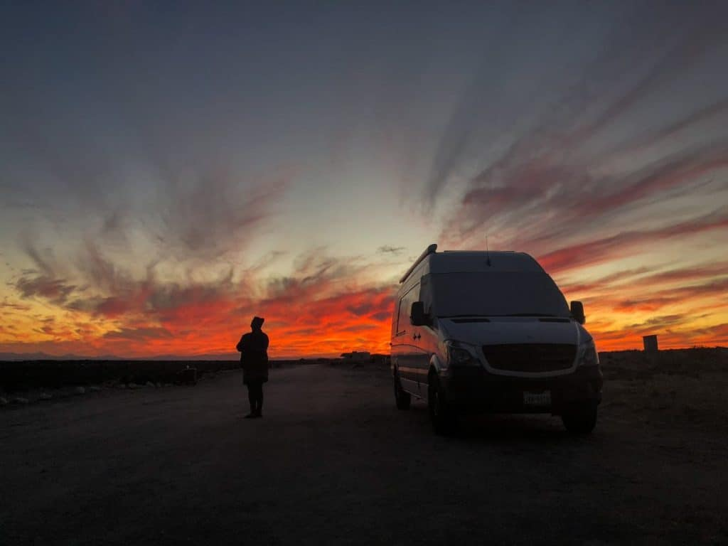 The sunsets behind the white Sprinter van with vibrant oranges and reds.