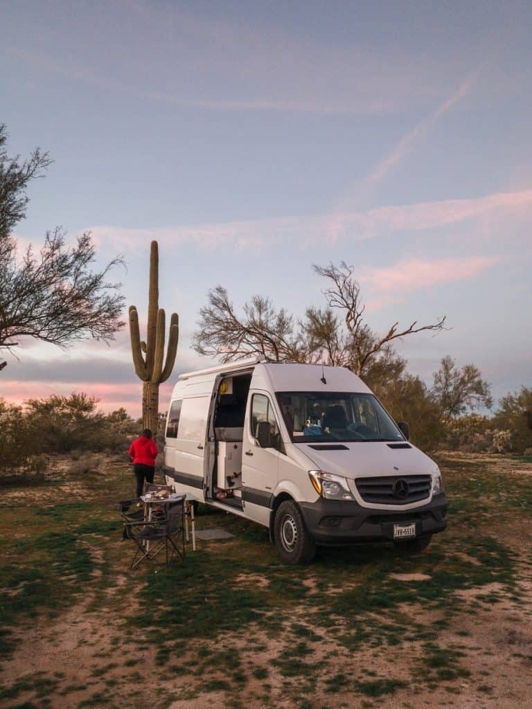 The van is camped out in the desert with a large saguaro cactus directly behind it. The side door is open, a table and two chairs sit out next to the side doors of the van.