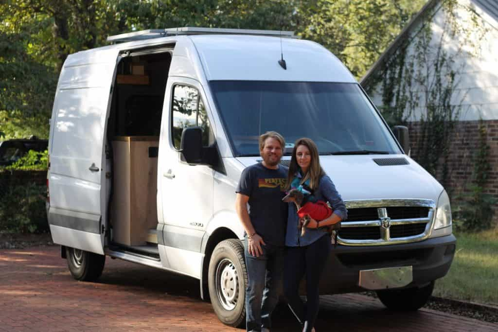 Guy and girl stand in front of their sprinter van holding their dachshund.
