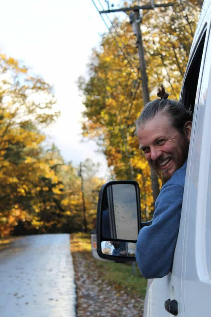 Guy leans out of driver side window looking back at the camera and smiling. Autumns changing leaves sparkle in the background.