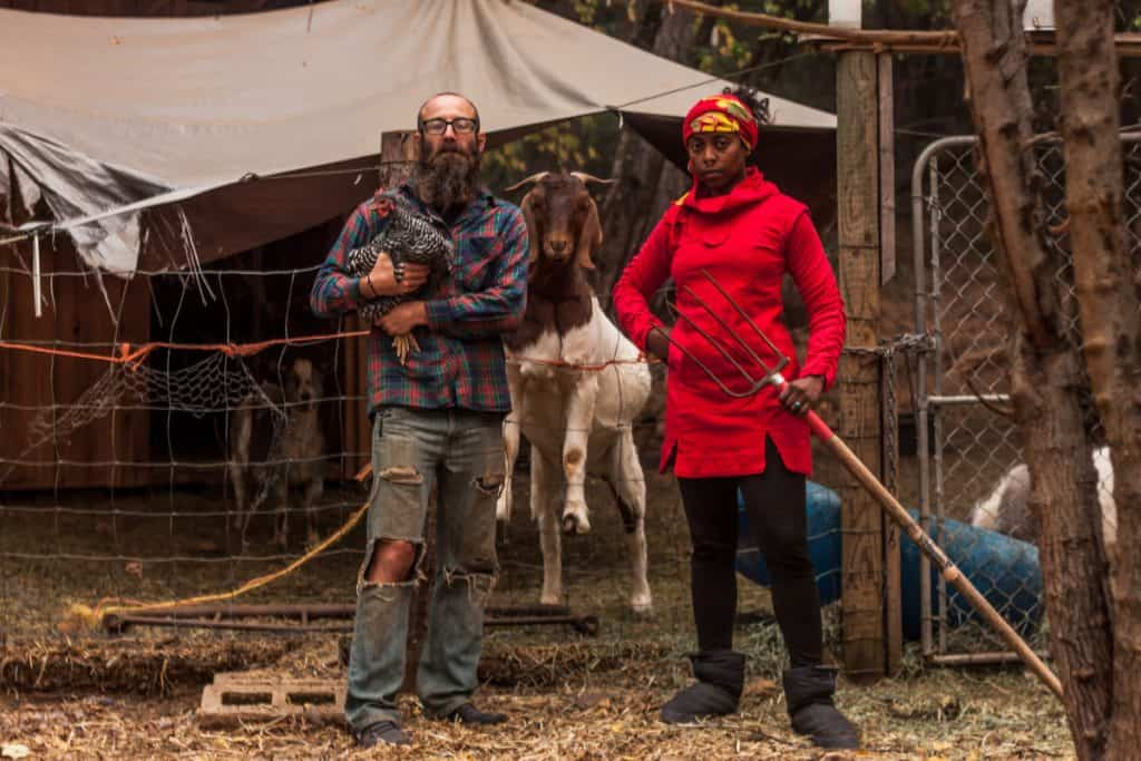 Man, woma, and goat stand facing the camera. The man holds a chicken and the woman holds a pitchfork. The goat looks condescendingly forward.