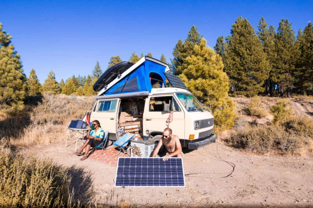 man sets up solar panel outside van