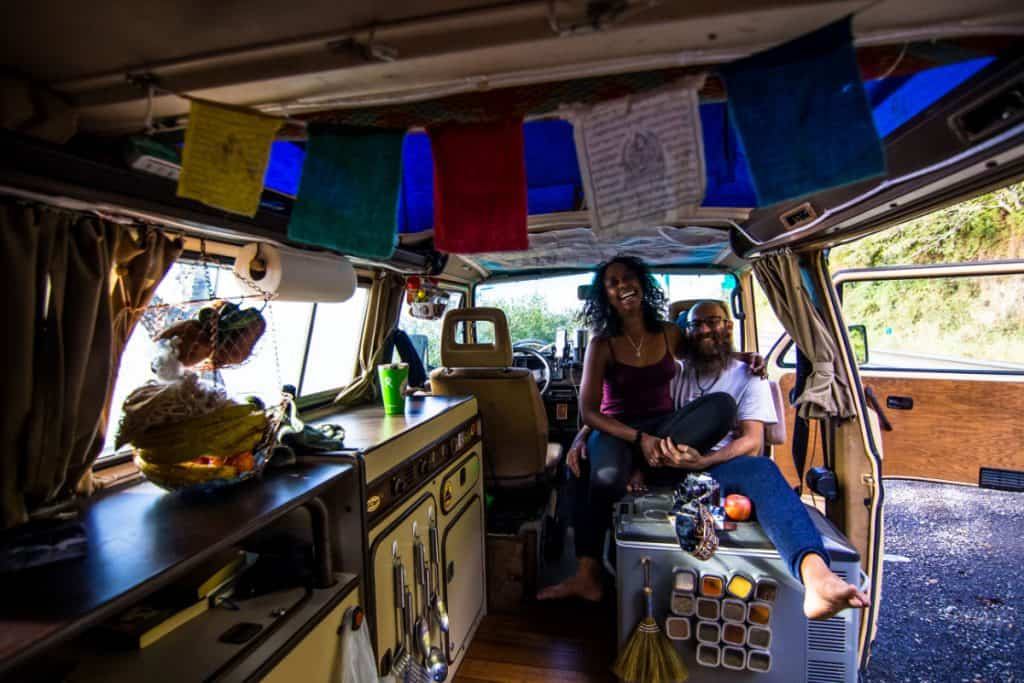 man and wife happily sit with each other inside their van