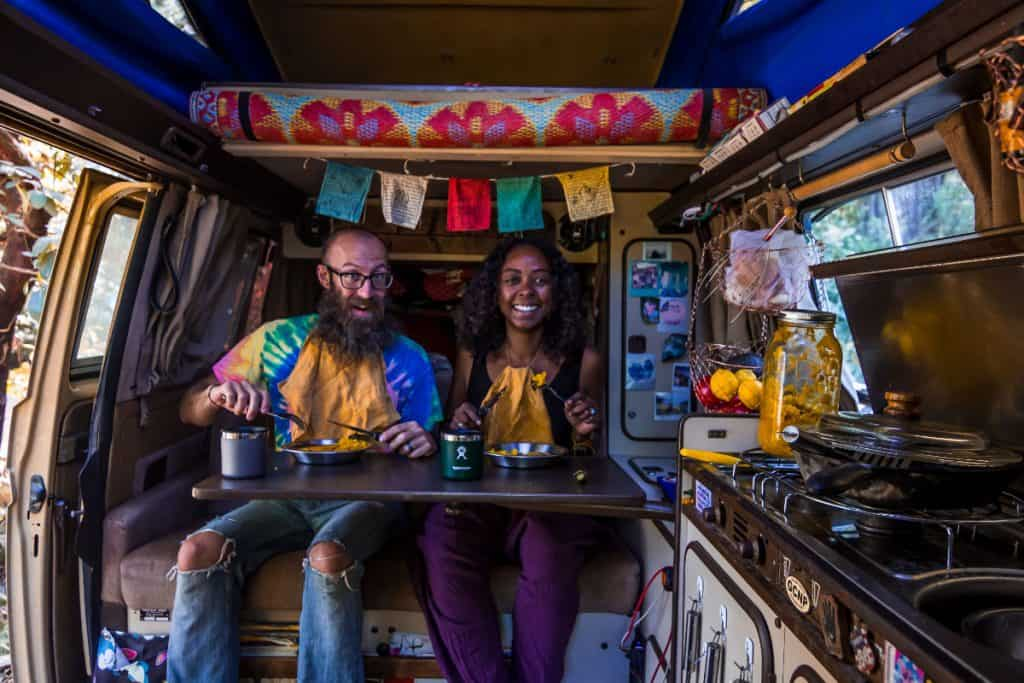 man and woman eat at fold out table inside vw campervan
