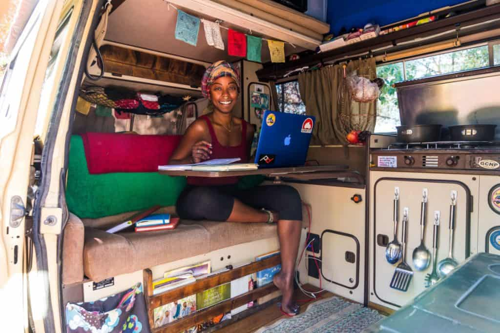 Woman works at a laptop inside of a westfalia van