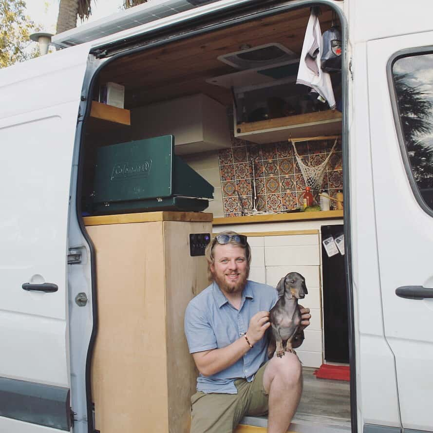 Guy sits on the side entrance of the van with his dachshund on his lap.