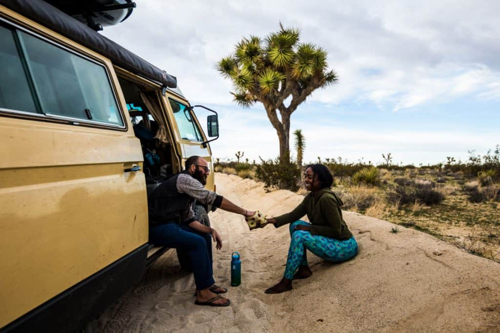 Man and woman hold hands outside of their campervan