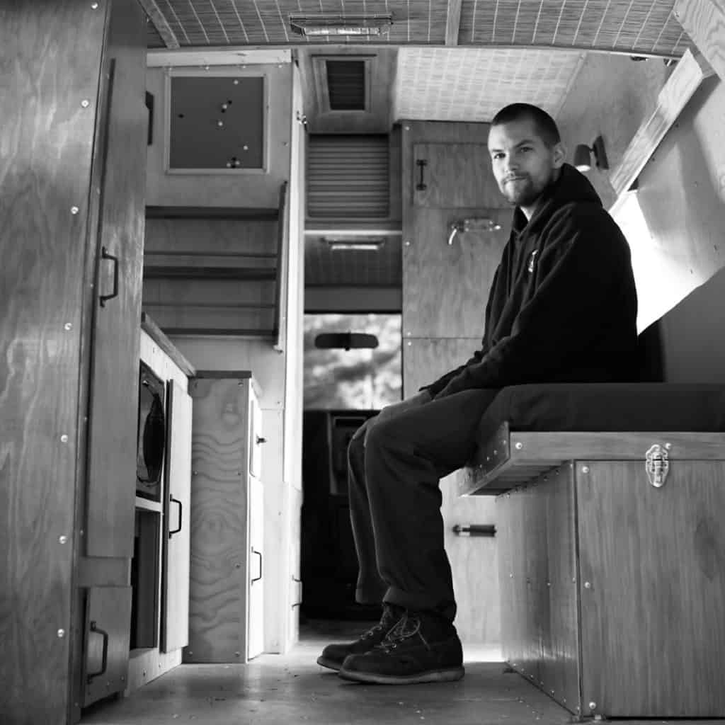 Black and white shot of a guy sitting on a couch inside of a van built out to be a tiny home.