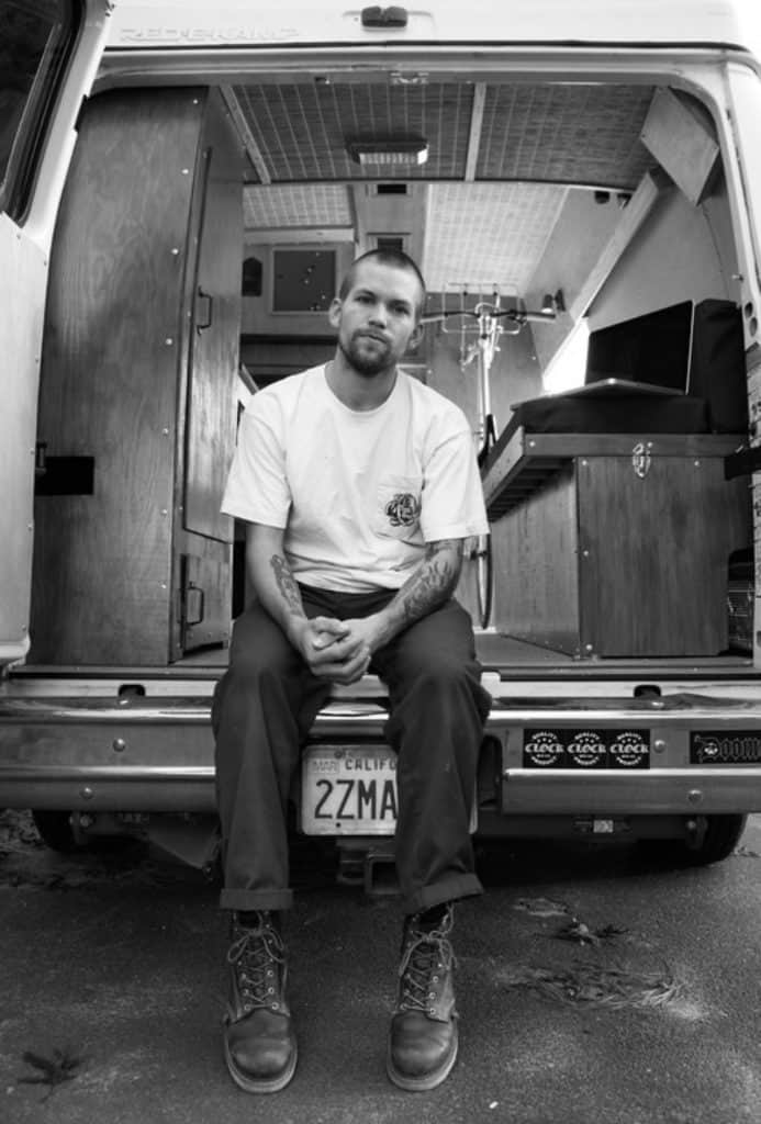 A white man with tattoos sits in the back of a van he built to be a tiny home. The image is black and white.