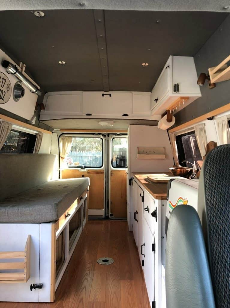 Interior shot of a van built to be a tiny home/ There is a couch to the left, a long walkway splits up the space, and the right is the kitchen counter. The top and bottom are filled with different types of cabinet storage.