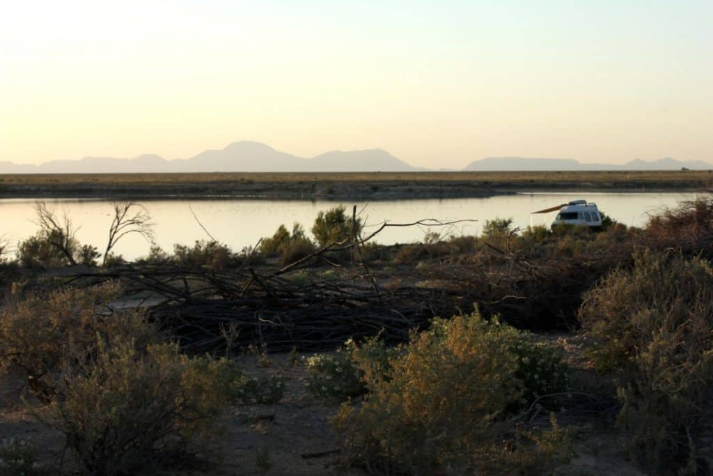 Van is parked in a quiet and secluded area on the water. There are mountains in the distance far past the water.