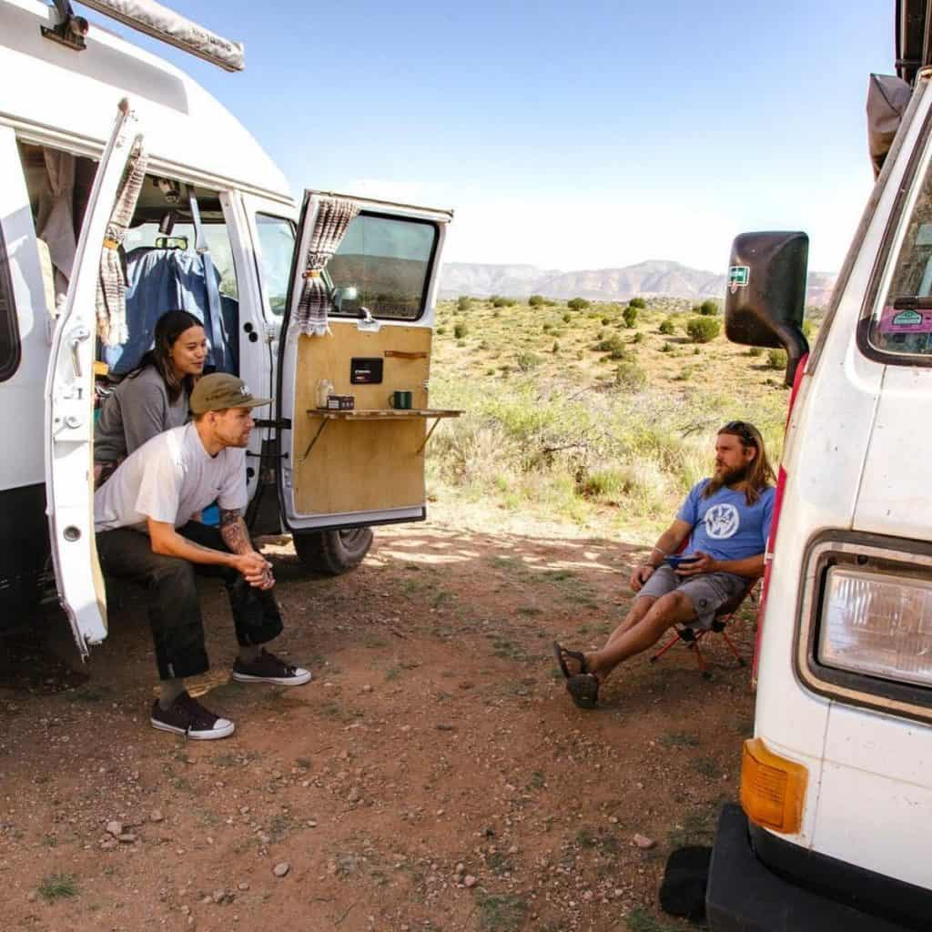 One girl and two guys sit around their vans chatting in the Arizona desert.