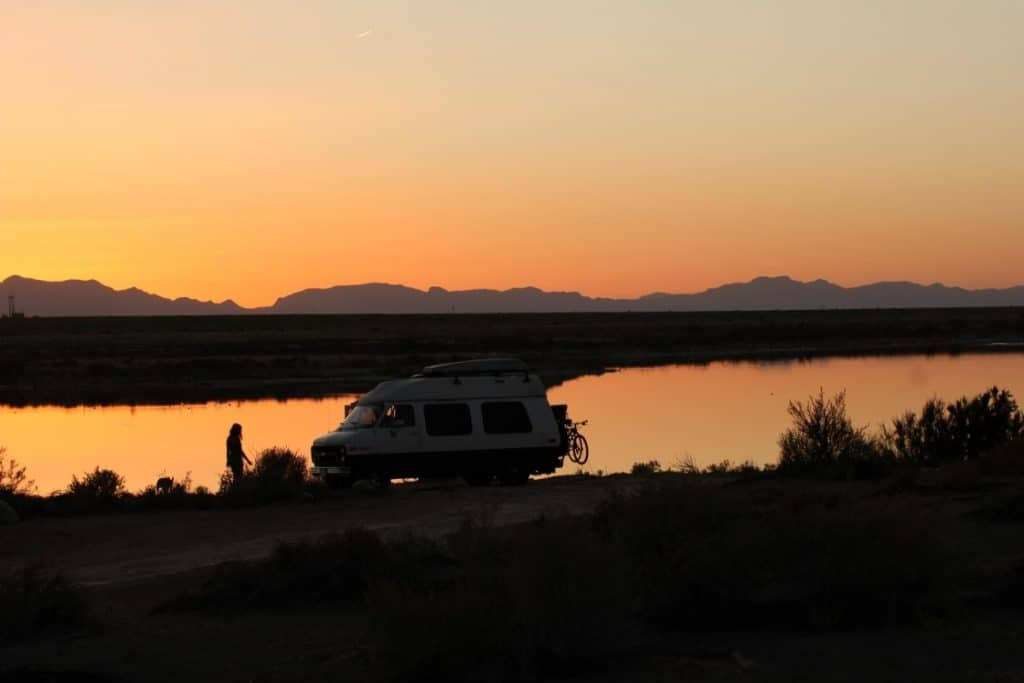 Van is parked on a beach near water as the sun sets over mountains in the distance.