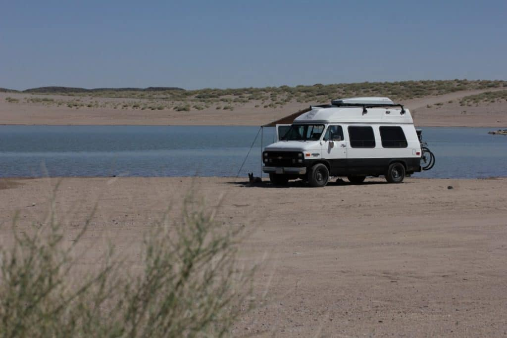 Van sits on a beach with the water right outside of it's open doors. Seems to be the only rig on the beach.