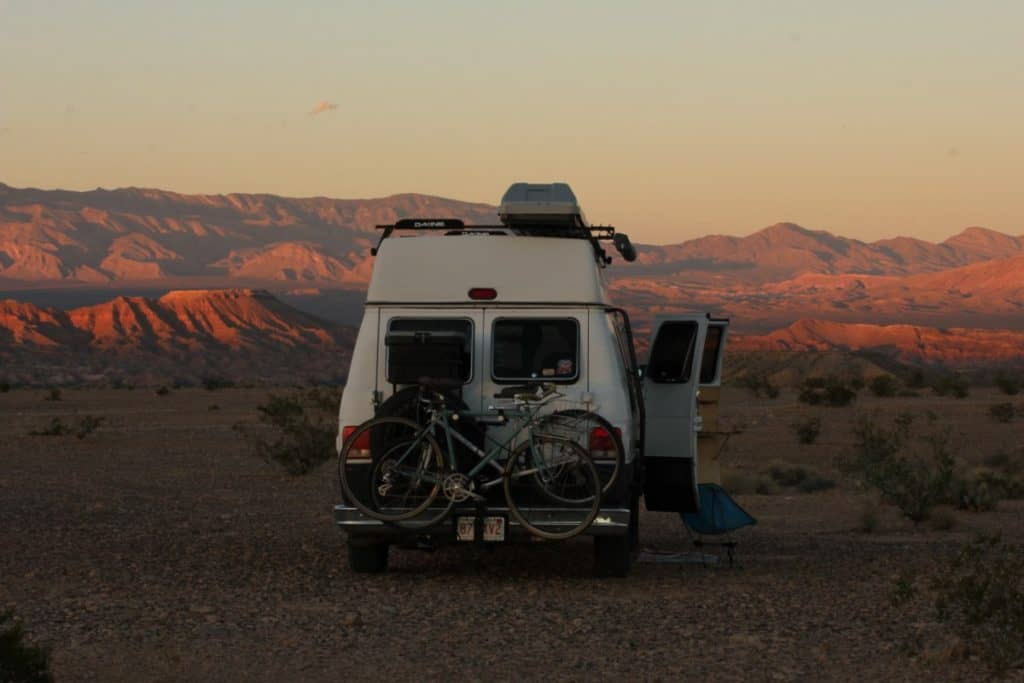 A shot of the back of a van. There are bikes mounted to the back. The side doors of the van are open and there is a chair on the ground in front of the doors. In the background of the shot is the sun setting over the beautiful red rocks of Nevada's mountains.