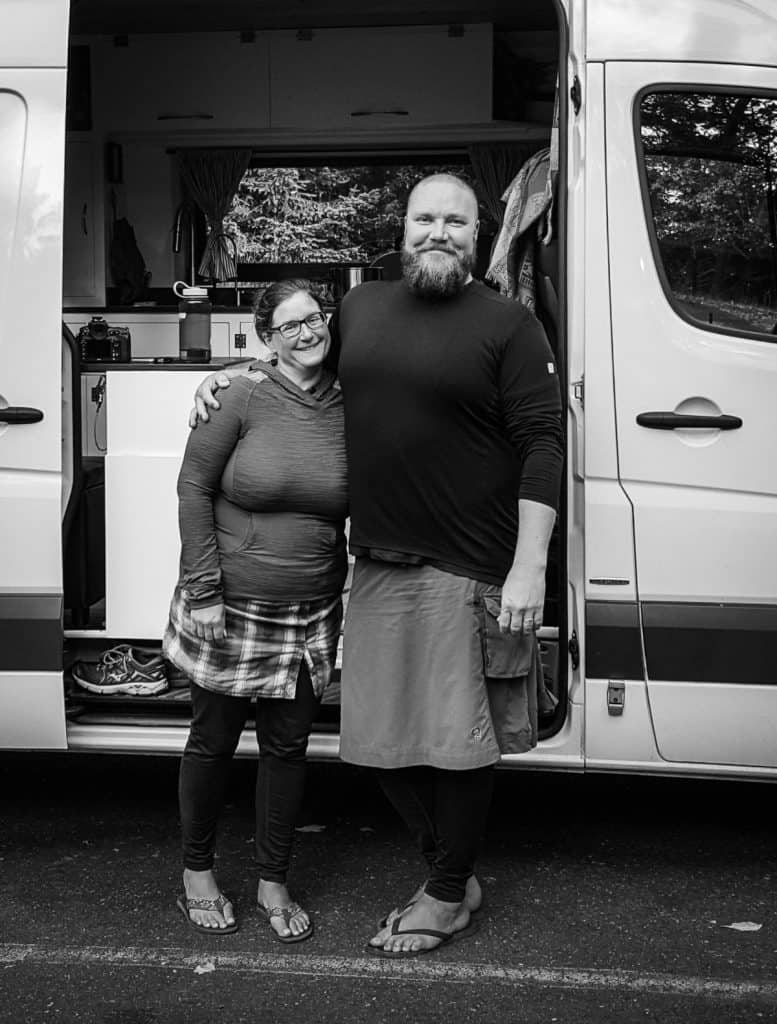 Man and woman happily pose in front of their white Sprinter van. The photo is in black in white.