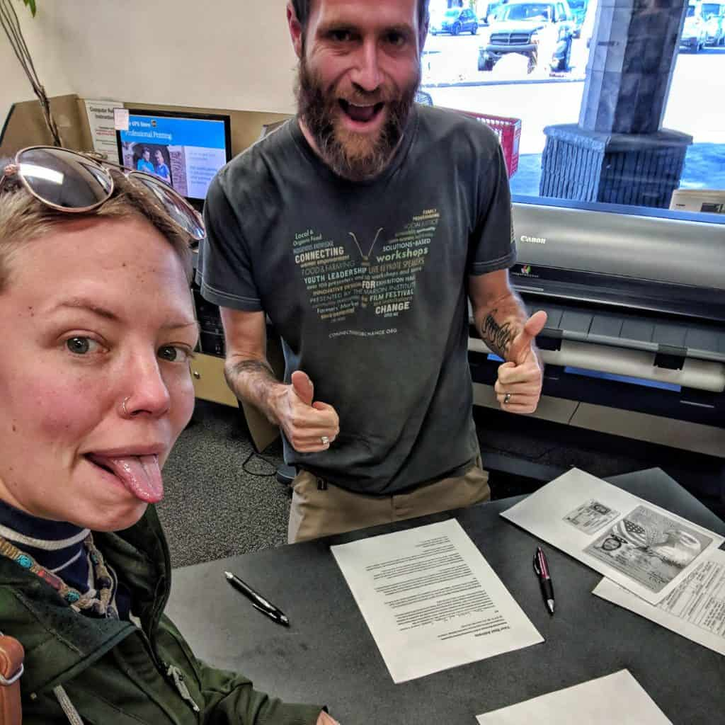 Man and woman signing paperwork with thumbs up