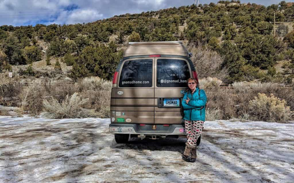 Jayme standing next to the van showing off the new SOuth Dakota license plates