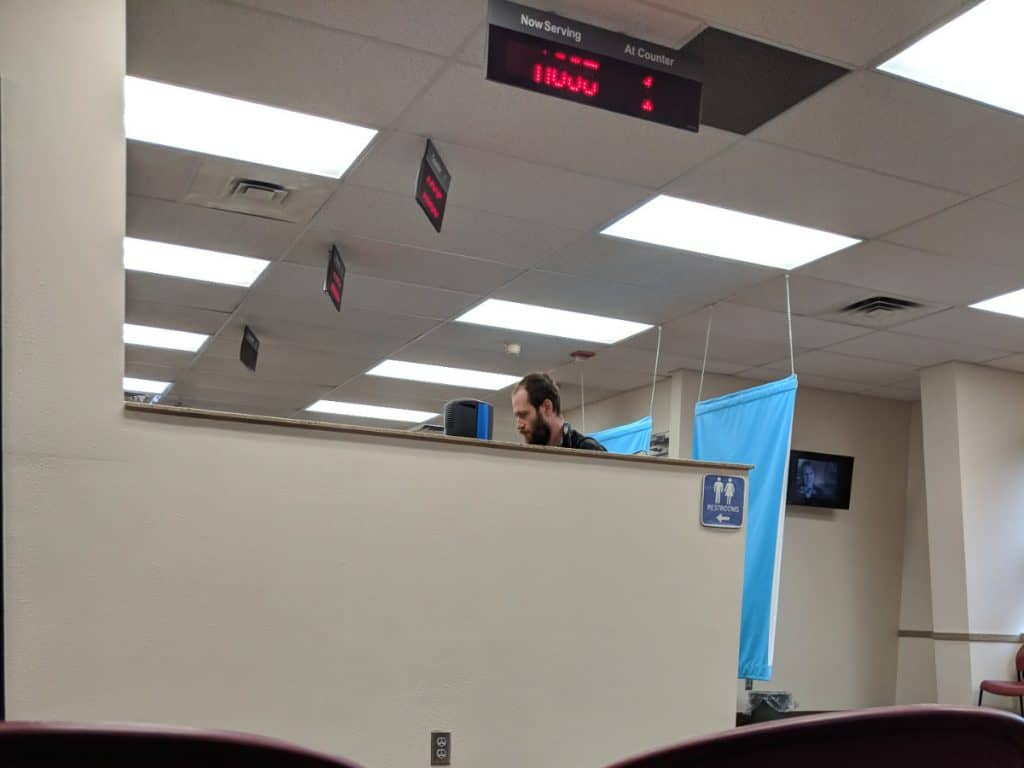 Man stands at the counter at a DMV office