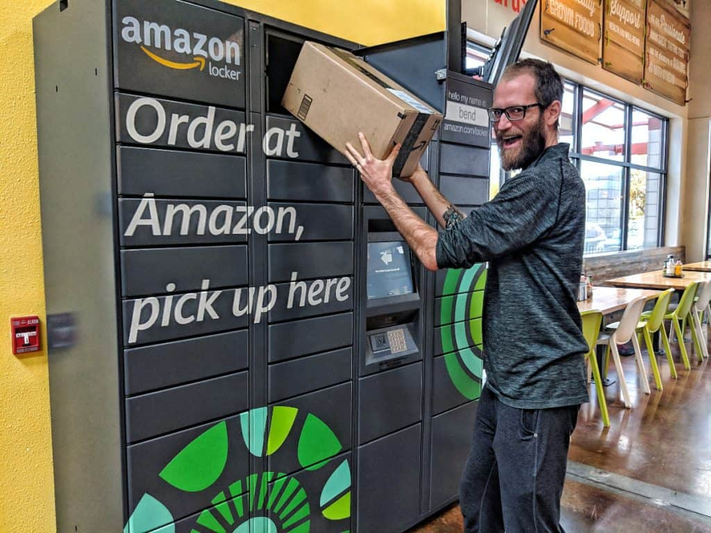 man happily removes a package from an amazon locker
