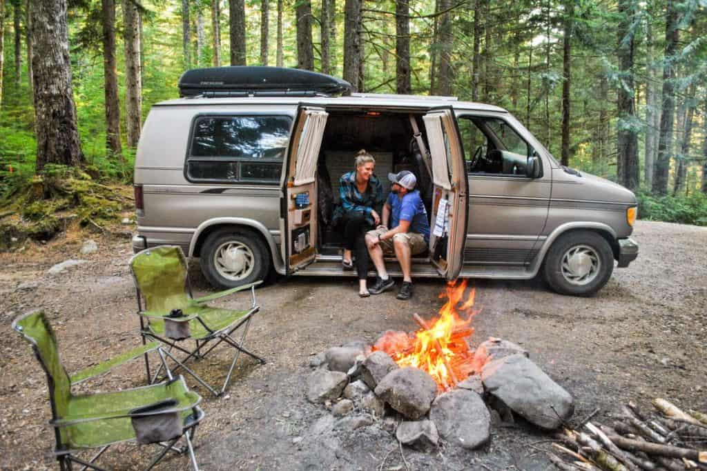 A girl and guy sit on the edge of their van where the side doors open. They are in the middle of the woods and a large campfire roars in front of them.