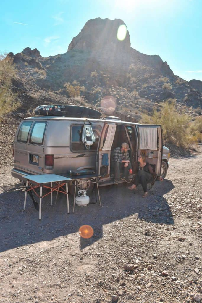 Guy and girl sit outside of their van with the side doors open and a large mountain view behind them. They have tables and a stove sitting out as well.
