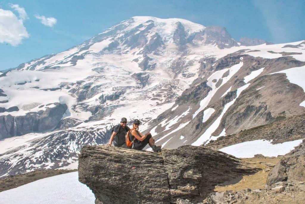 Guy and girl sit on a rock ledge with the peak of a snow capped mountain directly behind them.