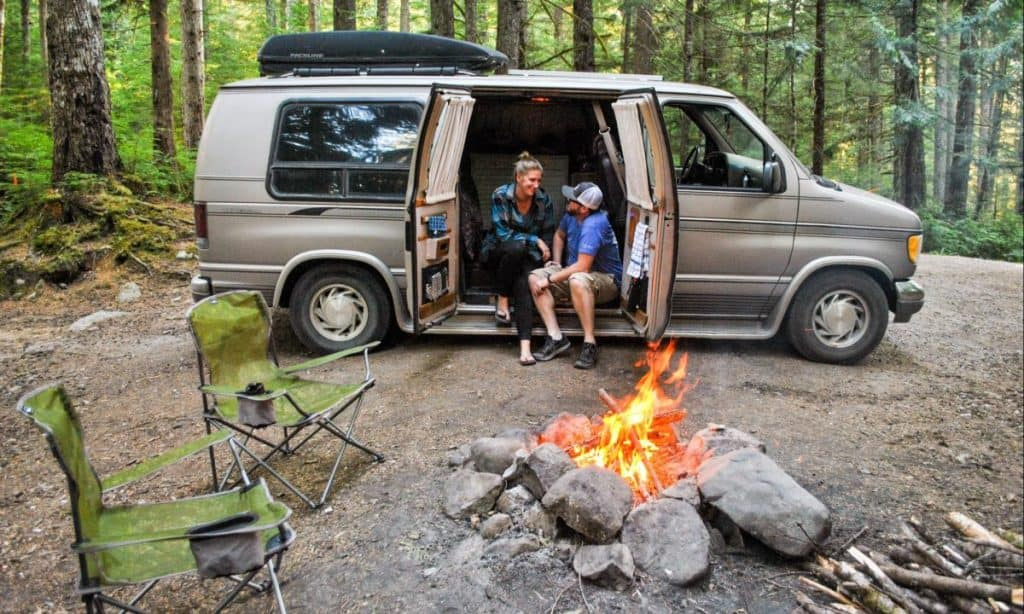 Couple sits on the edge of their van built to be a tiny home with their side doors open. There is a bonfire in front of them. They look at one another happily.