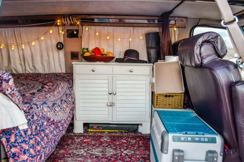 The interior of a van built to be a tiny home. It is a shot from the side doors looking in. We see a fridge behind the passenger seat and a dresser and some additional storage behind the drive seat. The bed begins on the left.