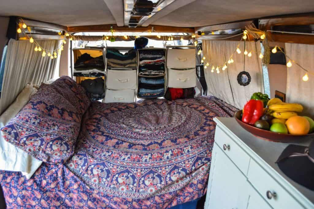 The interior of a van built into a tiny home. We see a large bed and clothing storage near the back of the van.