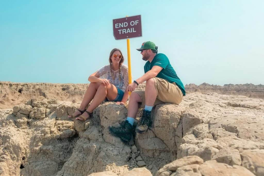"Girl and guy sit on small rock formation next to a sign that says ""END OF TRAIL""."