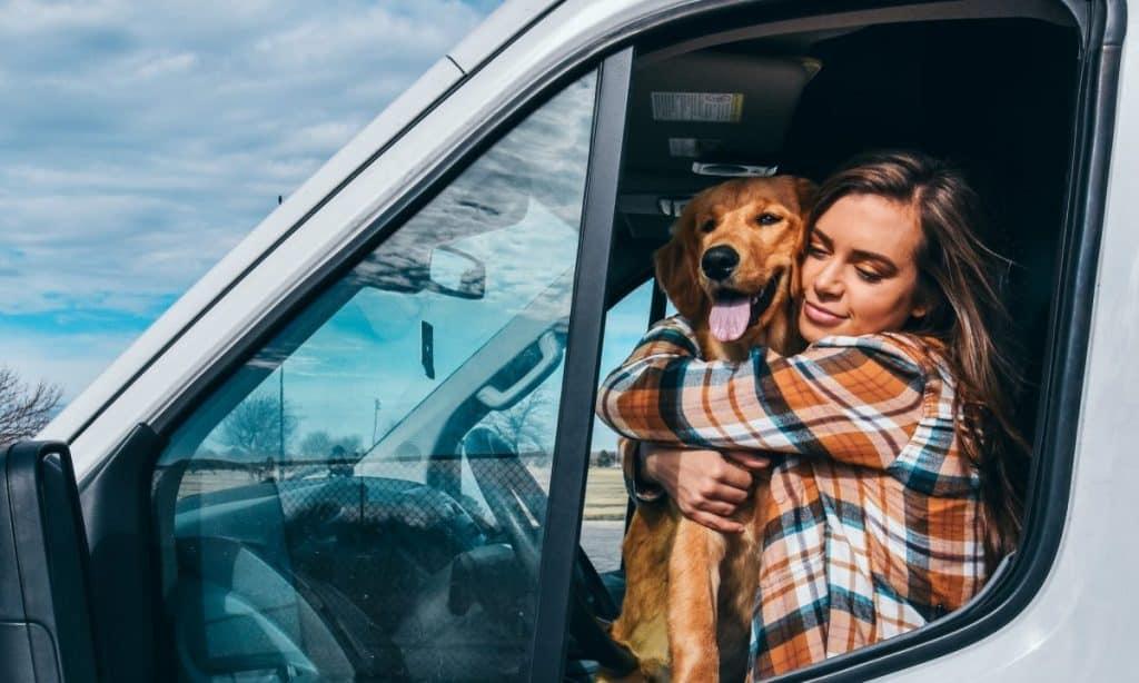 girl and dog hugging on driver seat of van