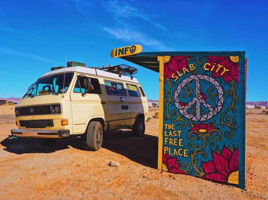 VW Van parked near slab city welcome sign
