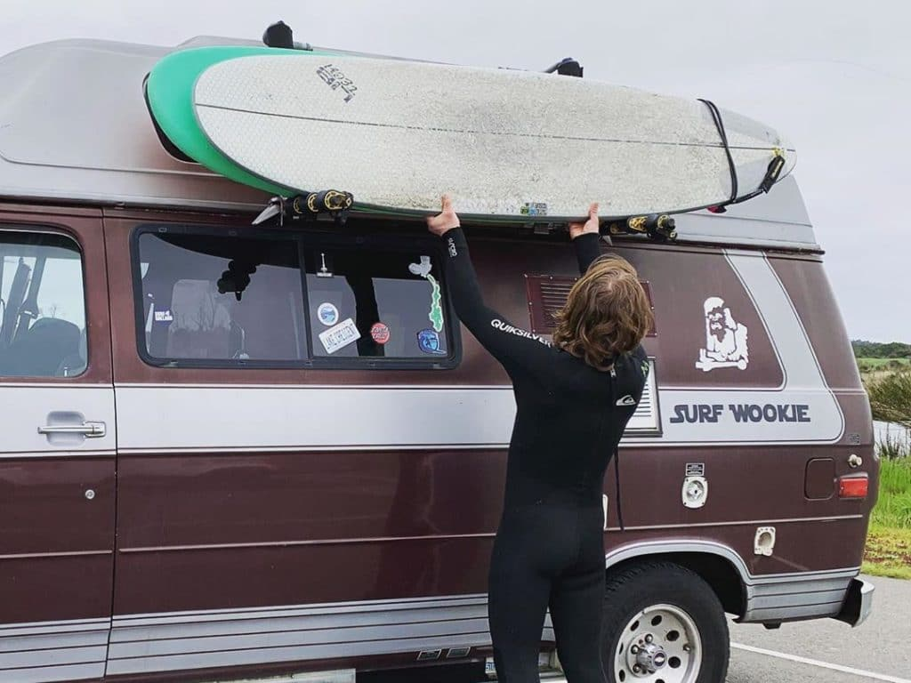 Man mounting surfboard to side of van