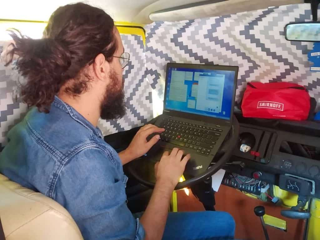 guy working on laptop on steering wheel