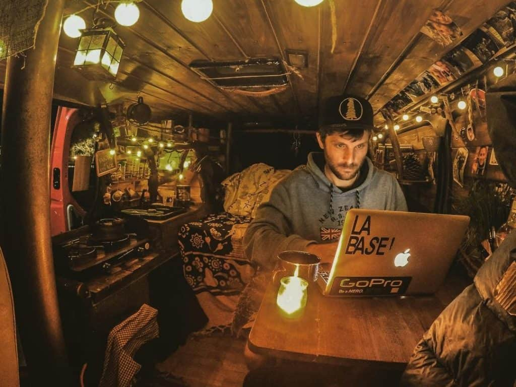man sits in front of computer working inside his van