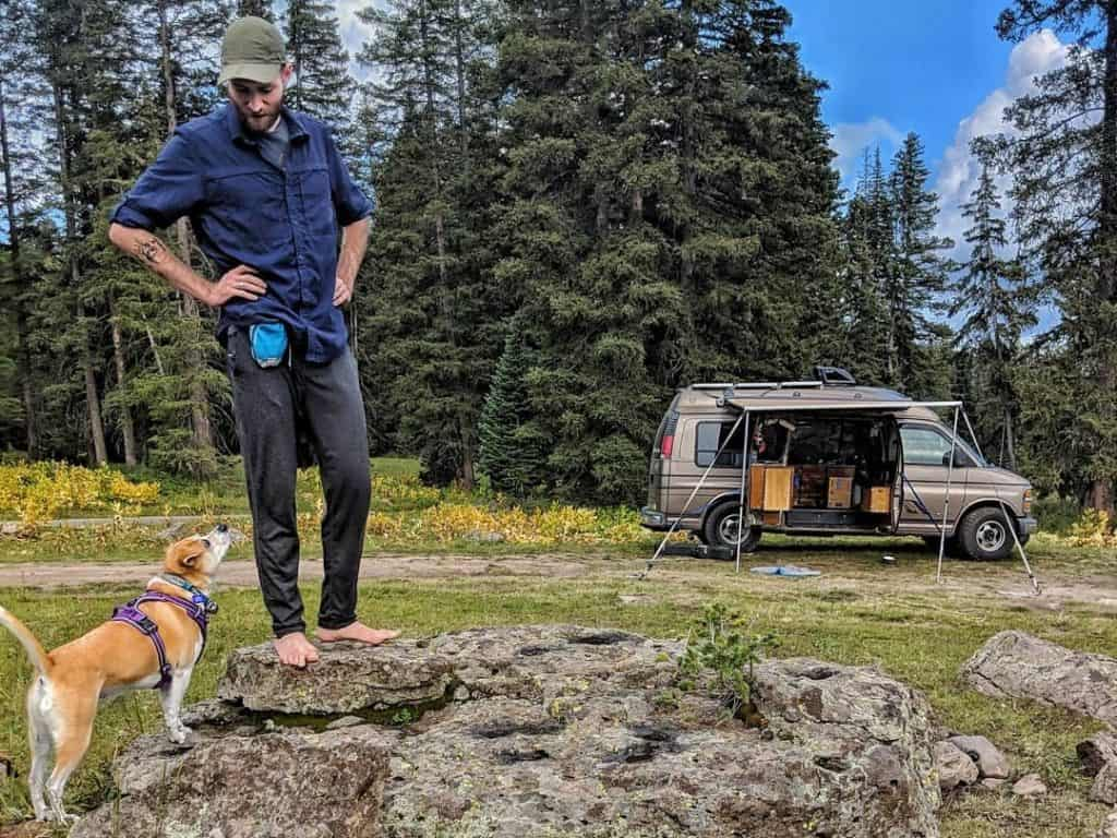 man stands on rock with dogs sniffing below him and van in the background
