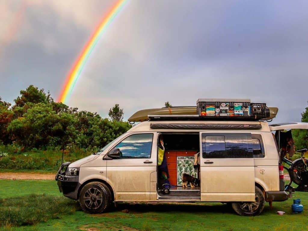 van camped with a rainbow behind it
