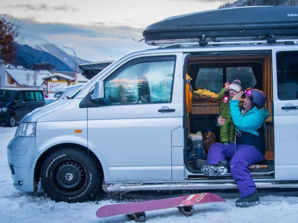 woman and child high five in van - van surrounded by snow