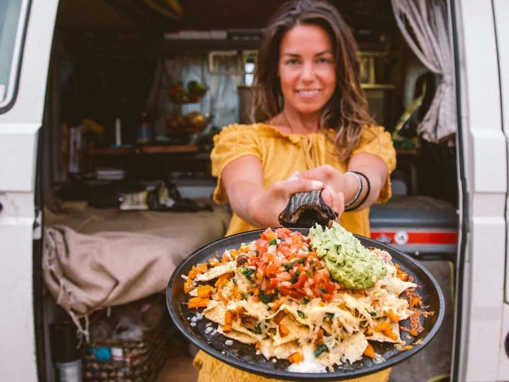 woman holds skillet of food outside of van