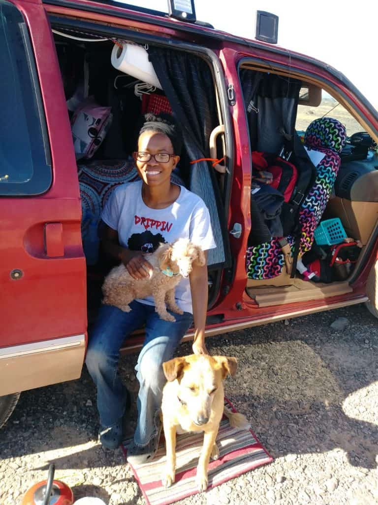 Crystal poses with two dogs while sitting on the edge of her red minivan