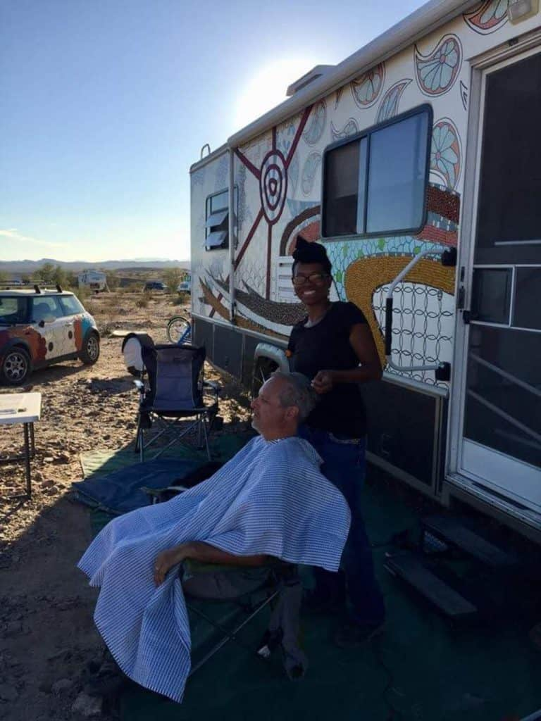 Crystal does an older man's hair outside of an RV